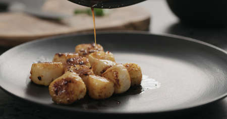 drizzle roasted scallops with juice from frying in black plate