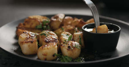 eat roasted scallops with baked potatoes on black plate