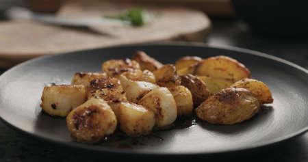 put baked potato wedges to roasted scallops on black plate Stok Fotoğraf