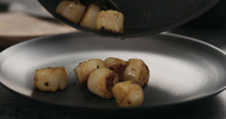 put roasted scallops on black plate