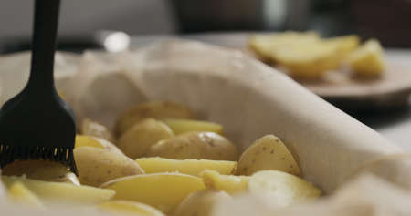 brush boiled potatoes with oil in a container with baking paper