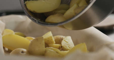 pour boiled potatoes in a container with baking paper