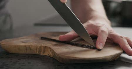Man cut vanilla pod on olive wood board