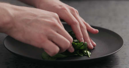 arrange spinach on black plate