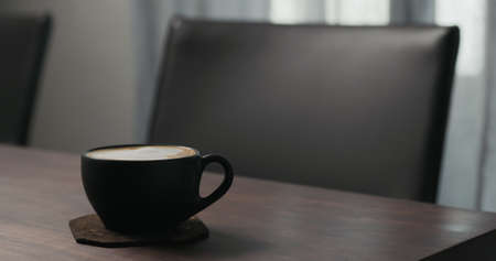 cappuccino in black cup on walnut table