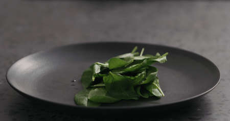 fresh spinach on black plate