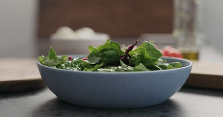 closeup making salad with mixed salad leaves in a blue bowl on concrete countertop