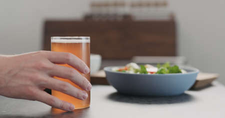man take soda drink from a bottle into highball glass on concrete countertop with copy space
