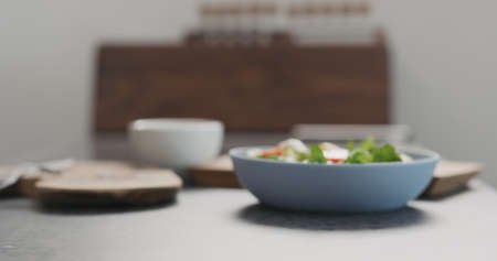 Blurred backgroiund of bowl with salad on concrete countertop