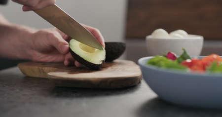 man slicing avocado for a salad on olive wood board Stok Fotoğraf