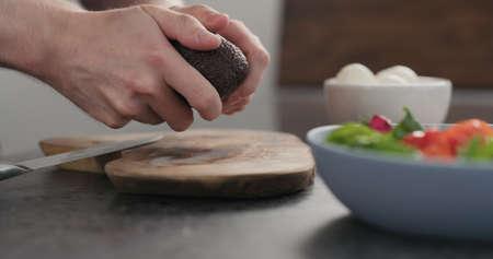 man open avocado for a salad on olive wood board Stok Fotoğraf