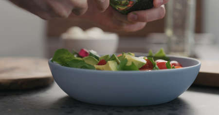 add avocado mixed salad leaves in a blue bowl on concrete countertop Stok Fotoğraf