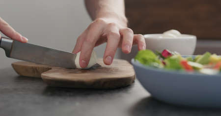 man cutting mozzarella balls on olive wood board
