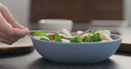 eat salad with avocado mixed salad leaves from a blue bowl on concrete countertop