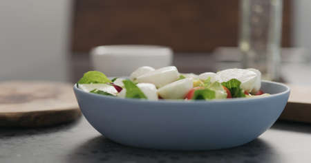 add mozzarella to mixed salad leaves in a blue bowl on concrete countertop Stok Fotoğraf