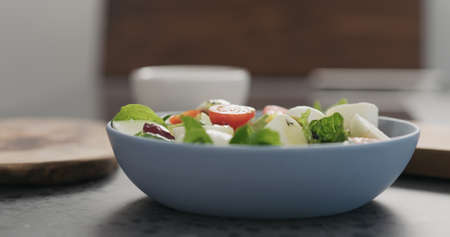 oil pour to salad with mozzarella and mixed salad leaves in a blue bowl on concrete countertop