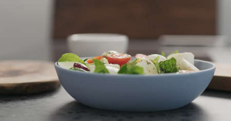 spices fall to salad with mozzarella and mixed salad leaves in a blue bowl on concrete countertop Stok Fotoğraf