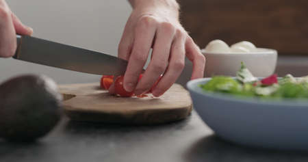 man cuts red cherry tomatoes on olive wood board