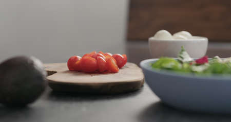 Closeup man takes tomato halves from olive wood