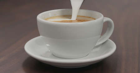 pour steamed milk into cappuccino white cup on walnut table
