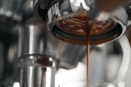 Extracting espresso with portafilter closeup