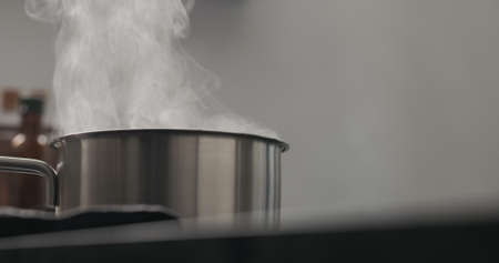 Slow motion steam rising from saucepan with copy space