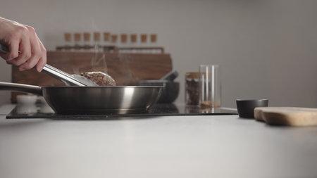 Man frying beef steak searing side on steel pan on electric hob on kitchen Banco de Imagens