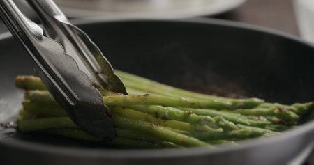 closeup of frozen asparagus cooking on nonstick pan