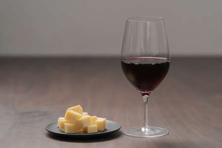 glass of red wine with vintage cheese on small plate