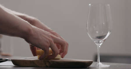 man hands cutting vintage cheese on oliveboard with wine glass