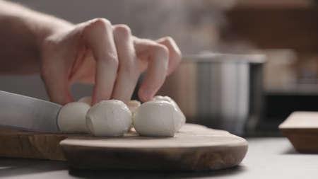 man slicing medium sized mozzarella balls with knife on olive wood board