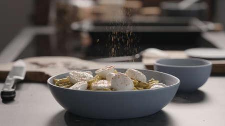 mozzarella to pesto penno in blue bowl on concrete countertop