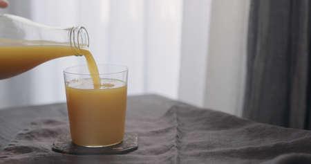 man pour orange juice from glass bottle into tumbler glass Zdjęcie Seryjne