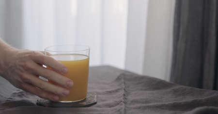 man take orange juice in tumbler glass