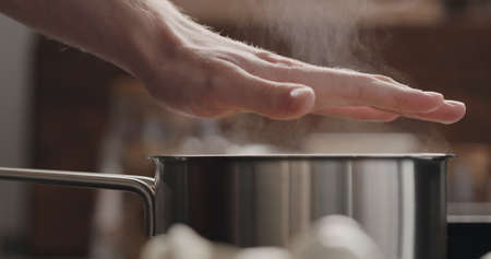 man handcheck temperature of steam rising from saucepan with boiling water on stove