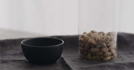salted pistachios with black bowl on linen cloth