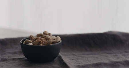 salted pistachios in black bowl on linen cloth