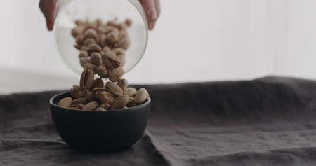 pour salted pistachios in black bowl on linen cloth