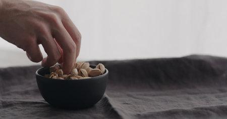 man hand take salted pistachios from black bowl on linen cloth Zdjęcie Seryjne