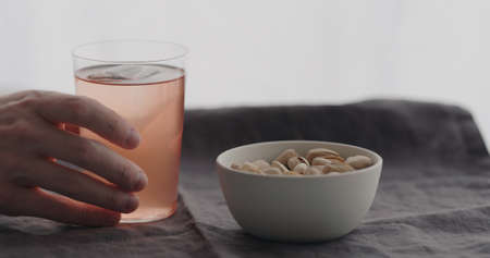 man drink peach lemonade served with salted pistachios