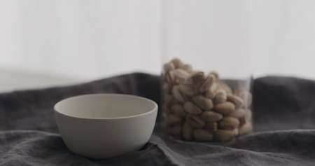 salted pistachios with white bowl on linen cloth