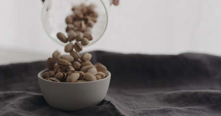 pour salted pistachios in white bowl on linen cloth Zdjęcie Seryjne