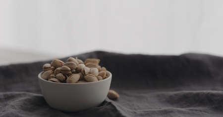 salted pistachios in white bowl on linen cloth Zdjęcie Seryjne