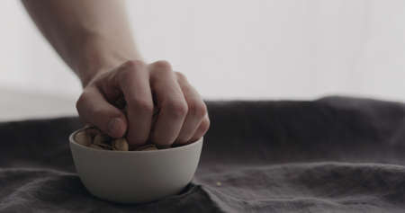 man hand take salted pistachios from white bowl on linen cloth