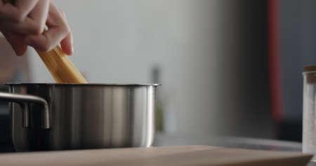 man hand put dried long fettuccine into saucepan with boiling water Zdjęcie Seryjne
