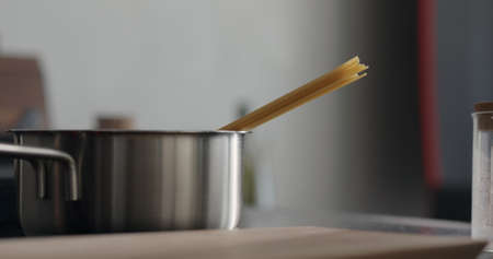dried long fettuccine into saucepan with boiling water