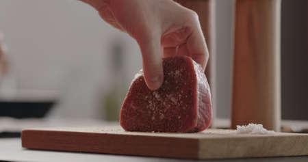 rubbing seasoning into beef steak on wood board