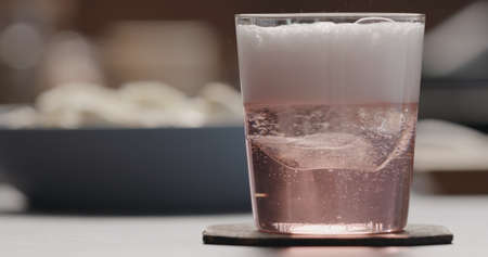 pour rose water over big ice rock into tumbler glass