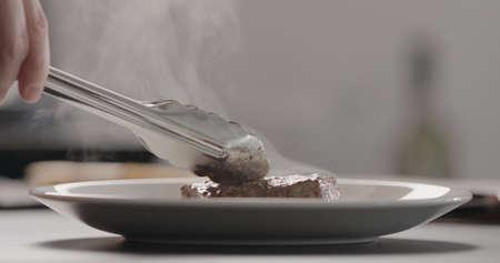man put hot steak on white plate