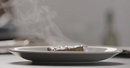 steaming hot steak on white plate